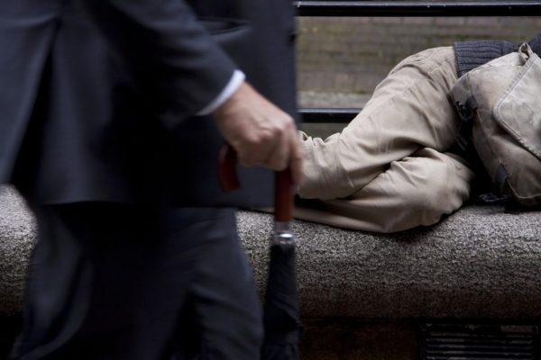 Arbeitslosigkeit aufgezeigt durch einen Reichen, der an einem Obdachlosen auf einer Bank liegend vorbei geht.