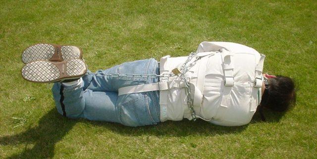 Mann in Zwangsjacke auf dem Boden liegend