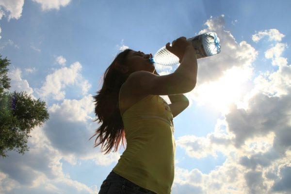 Frau gibt ihrer Durstsignale nach und trinkt Wasser aus einer Flasche