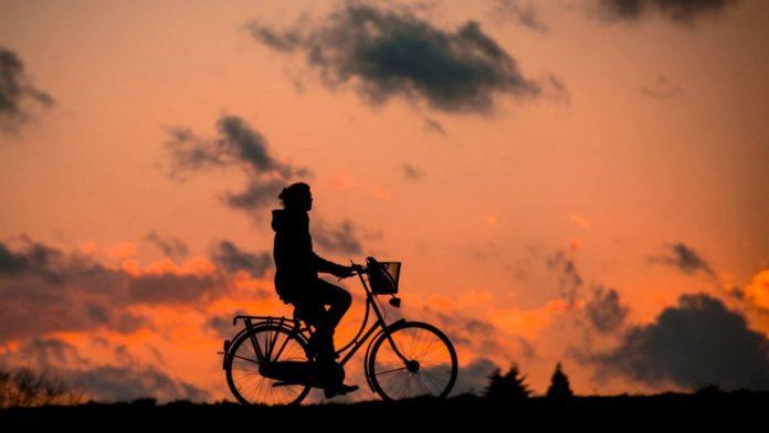 Frau fährt Fahhrad, Silhouette im Sonnenuntergang, Gesundheit und Fitness