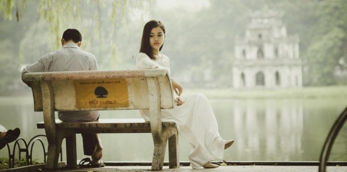 Asiatisches Paar sitzt getrennt auf einer Bank nach einem Streit