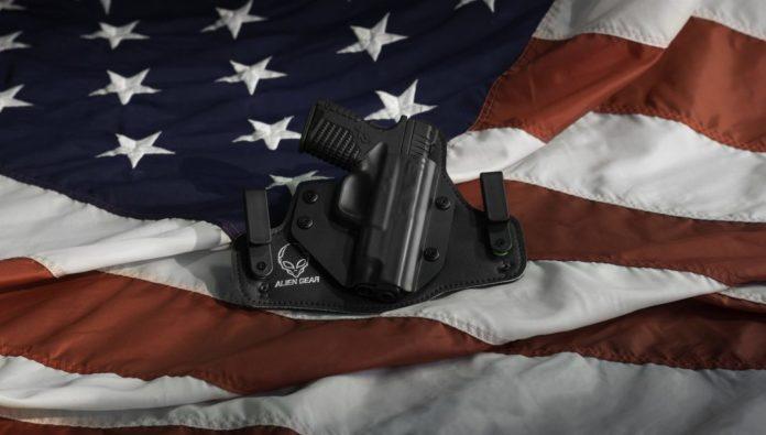 Pistole auf der Flagge vom Terrorstaat USA