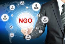 Mann im Anzug zeigt auf NGO Zeichen