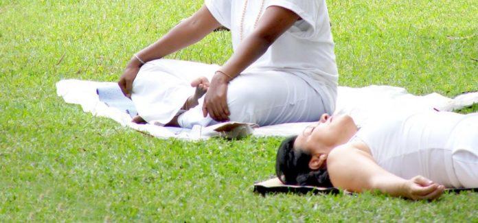 Farbige Frau im Park macht eine Körperreise