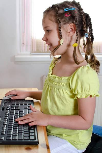 Mädchen sitzt am Schreibtisch mit Tastatur