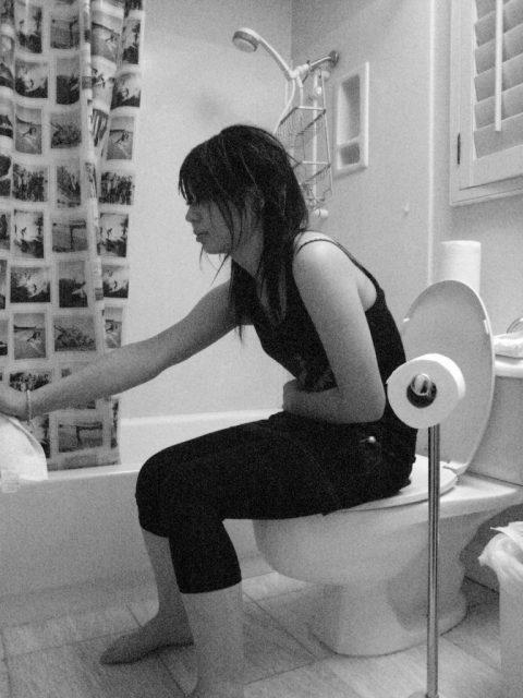 Mädchen sitzt mit Verstopfung auf Toilette