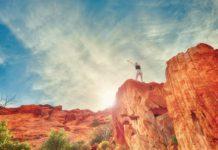 Frau streckt die Arme hoch auf einem Felsen sinnbildlich für nnere Stärke