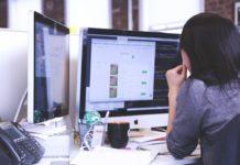 Frau am Schreibtisch mit 2 Computer bzw. screens