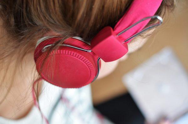Tinnitus durch zu laute Musik? Mädchen mit rosafarbenen Kopfhörern