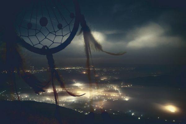 Traumfänger und Stadt bei Nacht im Hintergrund