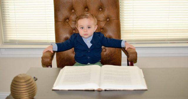 Vier-Punkt-Formel für Erfolg: Kleiner Junge im Chefsessel