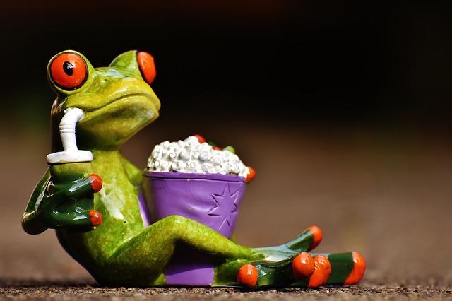 Frosch, der durch unterschwellige Werbung manipuliert wurde und Cola trinkt und Popcorn isst.