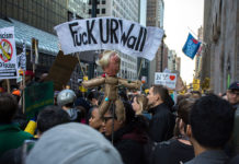 "Protests in New York City on April 14, 2016. One banner reads ""Fuck UR Wall"", denouncing Trump's policy on immigration"