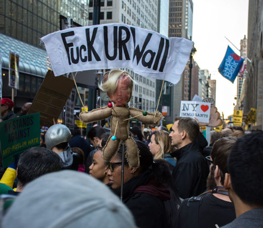 """Protests in New York City on April 14, 2016. One banner reads """"Fuck UR Wall"""", denouncing Trump's policy on immigration"""