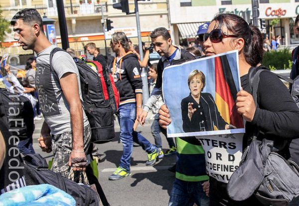 A womanl holds a picture of German Chancellor Angela Merkel as migrants set off on foot for the border with Austria from Budapest, Hungary, September 4, 2015.
