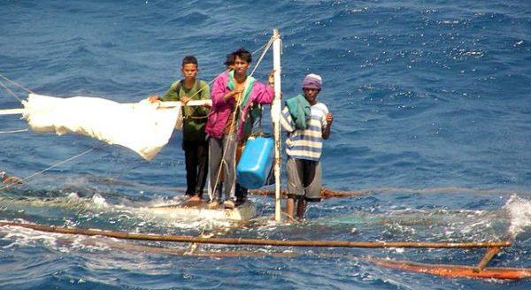 Philippinen, Vier Männer warten auf ihrem untergegangenen Boot auf Unterstützung von einem Navy-Schiff