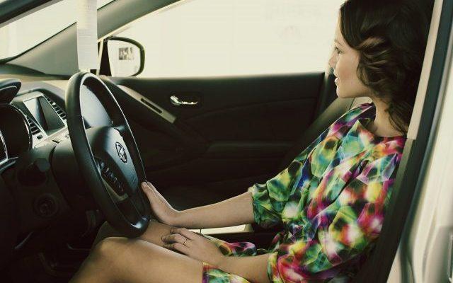Mädchen (die Person) sitzt am Steuer im Auto
