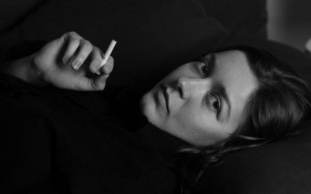 Frau die trauert mit Zigarette, als Beispiel für Nr. 3 der Fallstricke der Raucherentwöhnung