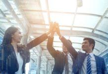 Drei Mitarbeiter geben sich high five nach einem Boni